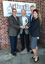 Jeff Rink, Vice President - Marketing & Business Development (L) and Charmian Hess, Production Underwriter - MD (R) presenting Arthur Hall with the Flagship Award.